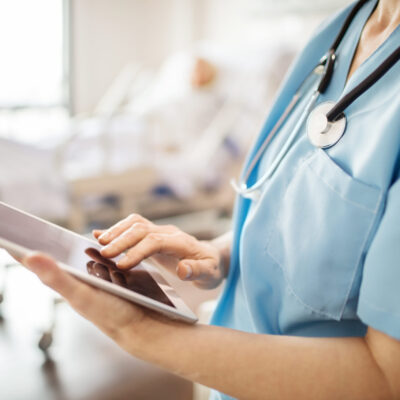 Midsection of female nurse using digital tablet in hospital. Close-up of medical professional is touching screen in ward. She is wearing scrubs.